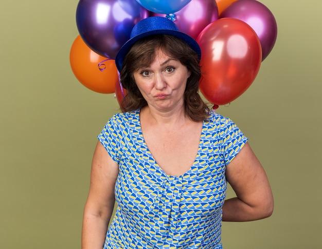 Femme d'âge moyen en chapeau de fête avec un tas de ballons colorés confus et mécontent de célébrer la fête d'anniversaire debout sur un mur vert