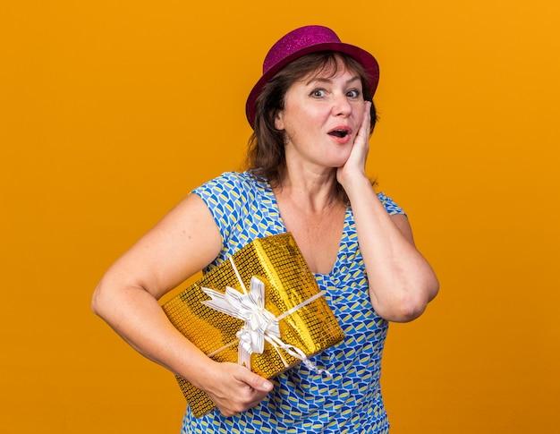 Femme d'âge moyen en chapeau de fête tenant un cadeau heureux et surpris célébrant la fête d'anniversaire debout sur le mur orange
