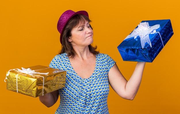 Femme d'âge moyen en chapeau de fête tenant des cadeaux d'anniversaire à la confusion ayant des doutes