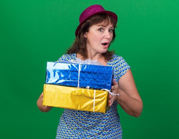 Femme d'âge moyen en chapeau de fête tenant des cadeaux d'anniversaire surpris célébrant la fête d'anniversaire debout sur un mur vert