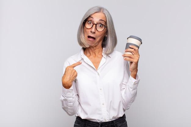 Femme d'âge moyen à choqué et surpris avec la bouche grande ouverte, pointant vers le concept de café auto