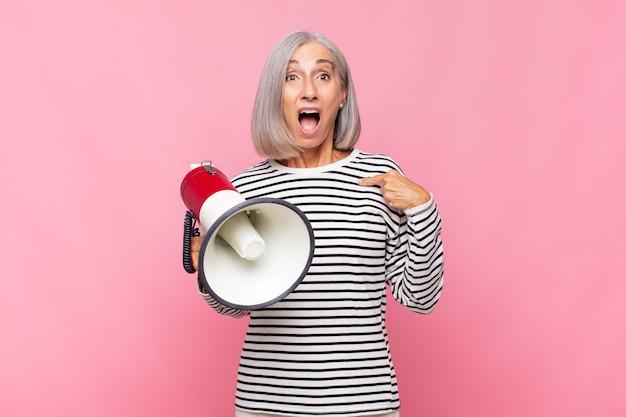 Femme d'âge moyen à choqué et surpris avec la bouche grande ouverte, pointant vers soi avec un mégaphone