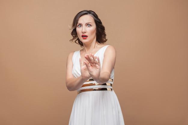 Femme d'âge moyen choquée effrayée regardant la caméra. femme exprimant ses émotions en robe blanche, lèvres rouges et coiffure frisée foncée. prise de vue en studio, à l'intérieur, isolée sur fond beige ou marron clair