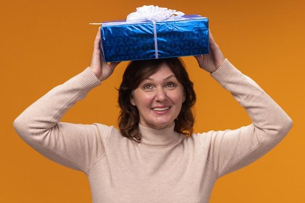 Femme d'âge moyen en col roulé beige tenant une boîte-cadeau au-dessus de sa tête heureux et excité debout sur un mur orange