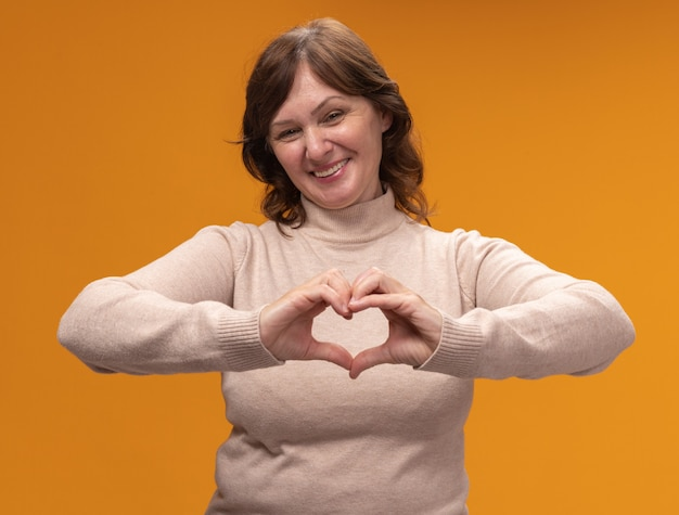 Femme d'âge moyen en col roulé beige avec visage hapy faisant le geste du cœur avec les doigts debout sur le mur orange