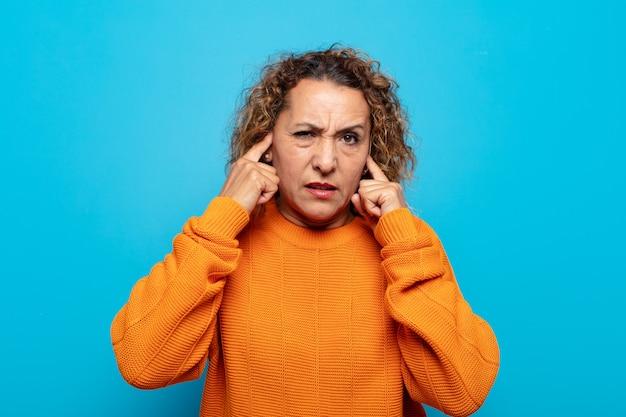 Femme d'âge moyen à la colère, stressée et agacée, couvrant les deux oreilles à un bruit assourdissant, un son ou une musique forte