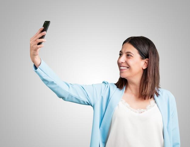 Femme d'âge moyen confiante et enjouée, prenant un selfie, regardant le mobile avec un geste drôle et insouciant, surfant sur les réseaux sociaux et sur internet