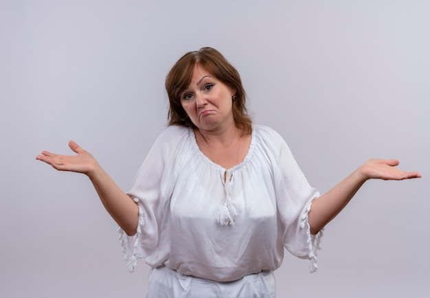 Femme d'âge moyen confus montrant les mains vides sur un mur blanc isolé