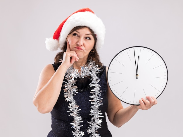 Femme d'âge moyen confuse portant un bonnet de noel et une guirlande de guirlandes autour du cou tenant une horloge en gardant la main sur le menton en levant isolé sur fond blanc