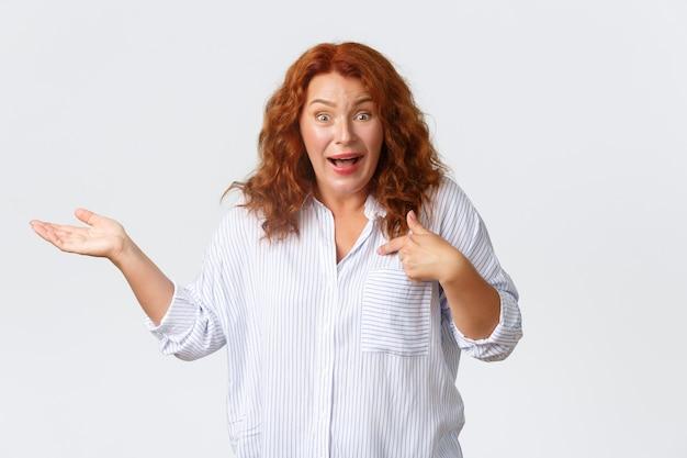 Une femme d'âge moyen confuse et surprise réagit aux accusations absurdes, se pointant du doigt et lève la main sur le côté sans aucune idée, debout perplexe sur un mur blanc.