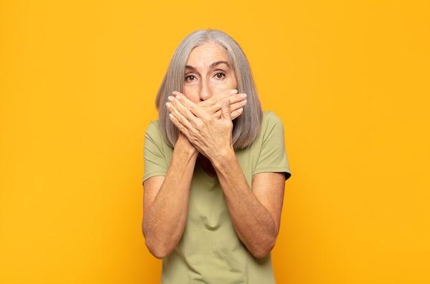 Femme d'âge moyen couvrant la bouche avec les mains avec une expression choquée et surprise, gardant un secret ou disant oops