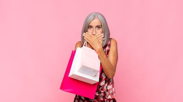 Femme d'âge moyen couvrant la bouche avec les mains avec une expression choquée et surprise, gardant un secret ou disant oups avec des sacs à provisions