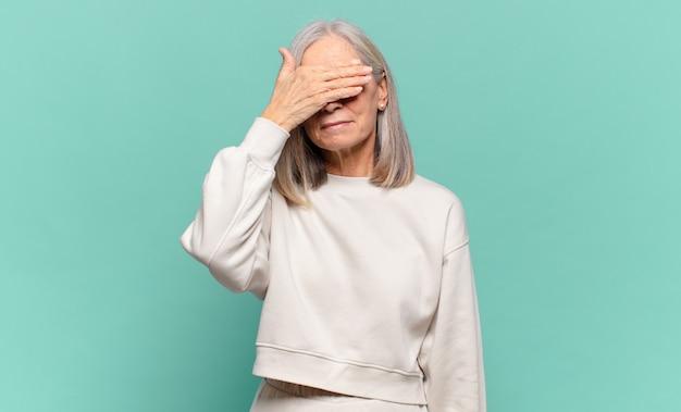 Femme d'âge moyen couvrant les yeux d'une main se sentant effrayée ou anxieuse, se demandant ou attendant aveuglément une surprise