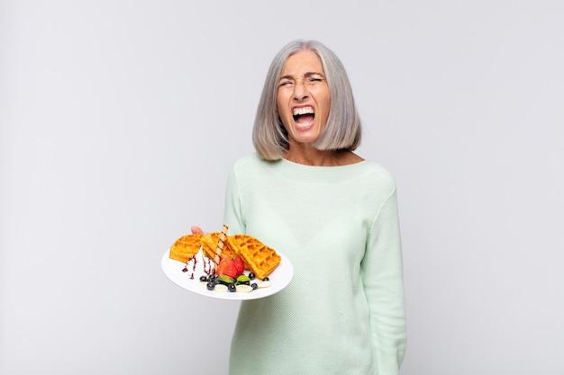 Femme d'âge moyen criant agressivement, l'air très en colère, frustré, indigné ou agacé, criant non. concept de petit déjeuner