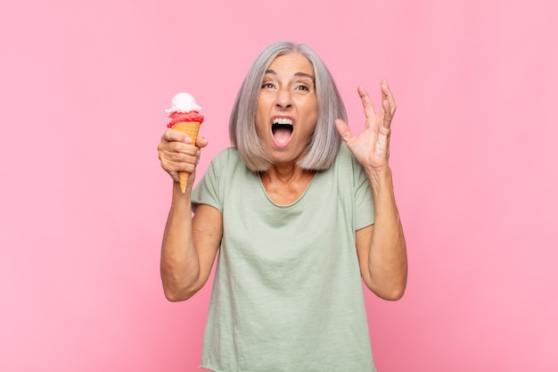 Femme d'âge moyen crier avec les mains en l'air, se sentir furieux isolé