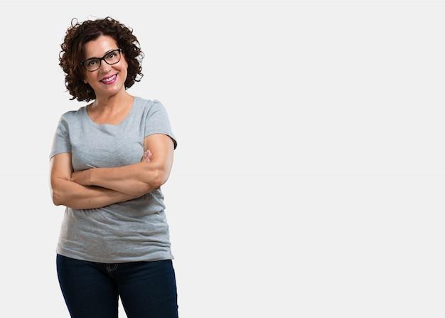 Femme d'âge moyen croisant les bras, souriante et heureuse, confiante et amicale