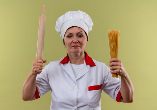 Femme d'âge moyen cuisinier en uniforme de chef holding rouleau à pâtisserie et spaghetti sur mur vert isolé