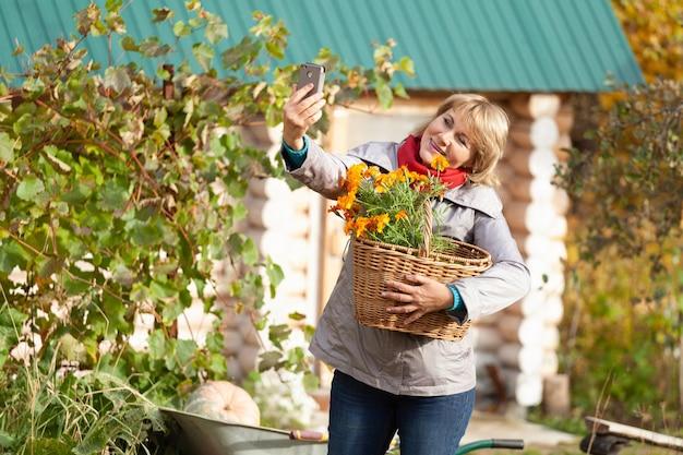 Une femme d'âge moyen dans le jardin à l'automne faisant le traitement du jardin