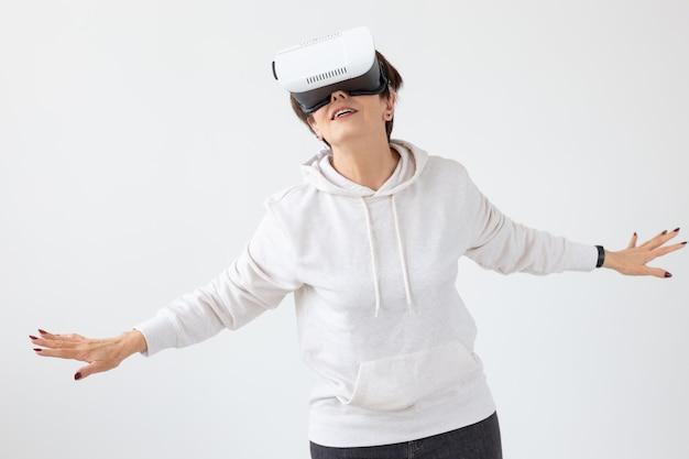 Femme d'âge moyen dans un pull léger joue à un jeu publicitaire avec des lunettes de réalité virtuelle