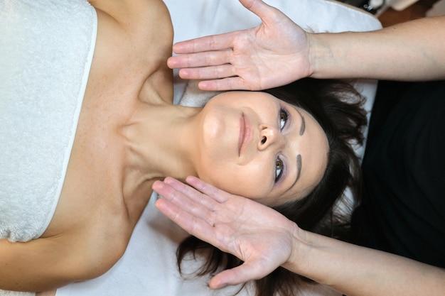 Femme d'âge moyen dans un salon de beauté spa, allongée sur une table de massage. massage du visage et du cou en gros plan. soins du corps et du visage, soins de santé, traitement, cosmétologie, femmes mûres