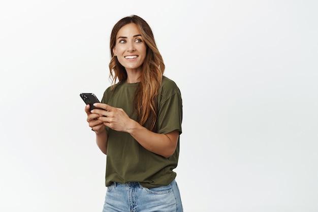 Femme d'âge moyen discutant, envoyant un message texte via un smartphone, regardant de côté avec un visage souriant et heureux