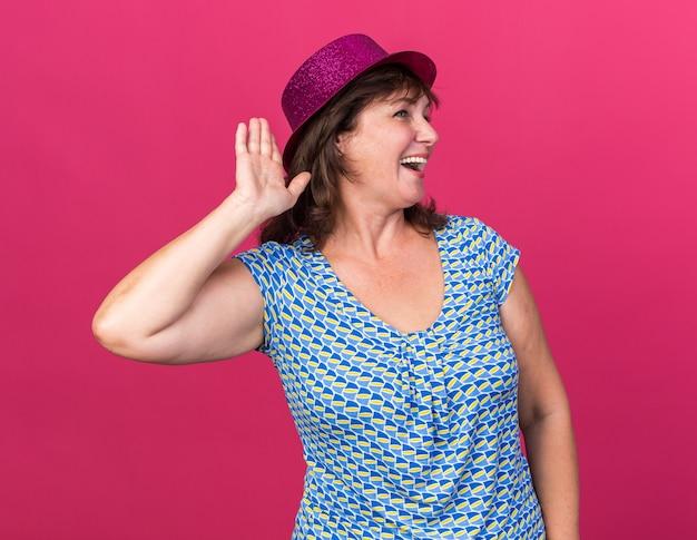 Femme d'âge moyen drôle en chapeau de fête regardant de côté avec la main sur l'oreille souriant gaiement