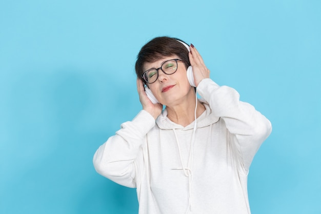Femme d'âge moyen, écouter de la musique sur un mur coloré.