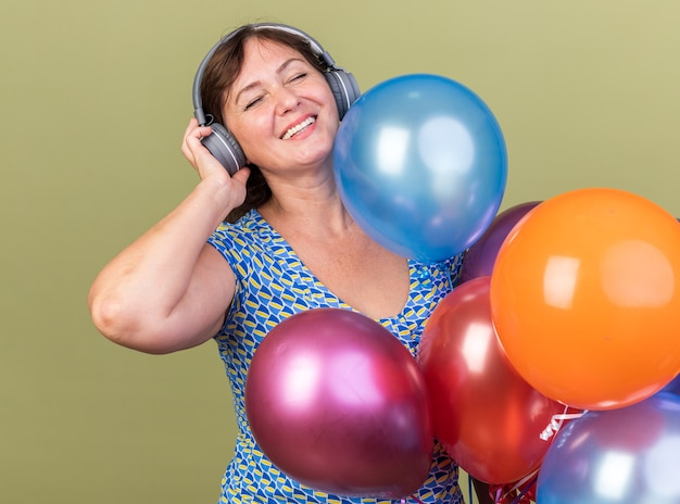 Femme d'âge moyen avec des écouteurs et un tas de ballons colorés heureux et joyeux appréciant sa musique préférée