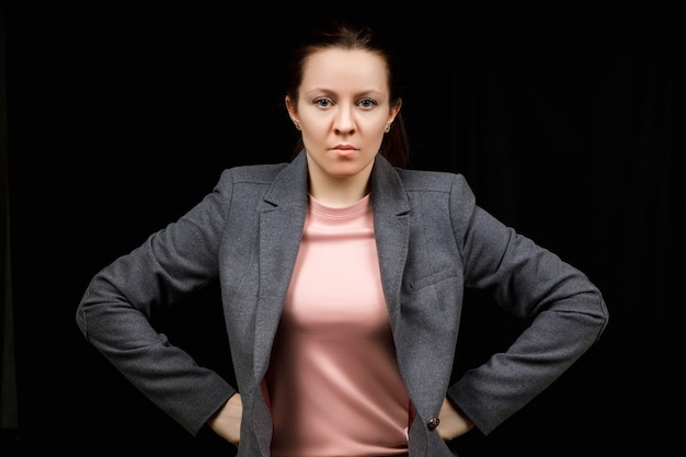 La femme d'âge moyen est en colère. la fille porte des vêtements décontractés plus doux sur un noir. femme maléfique, les mains sur les côtés.
