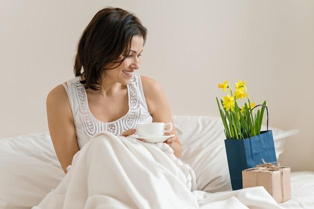 Femme d'âge moyen est heureux avec cadeau, bouquet de fleurs, assis dans le matin au lit avec une tasse de café.