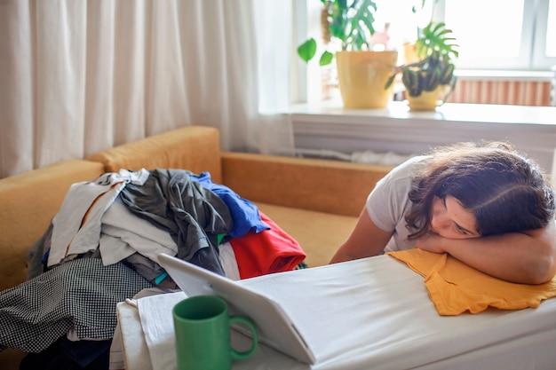 Une femme d'âge moyen fatiguée regarde une vidéo sur une tablette et repasse des objets ménagère et maman épuisée