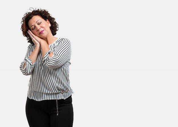 Femme d'âge moyen fatiguée et très fatiguée, regardant à l'aise et détendue, geste de sommeil