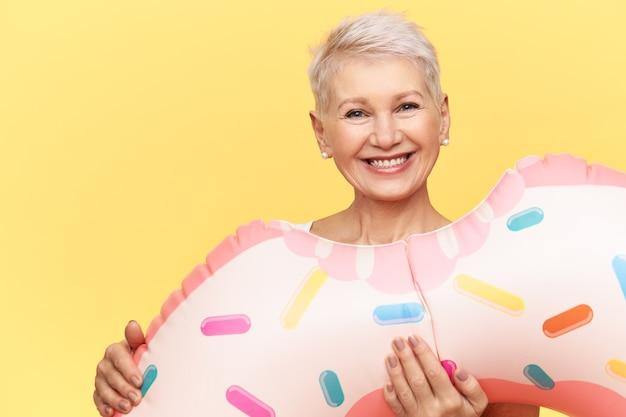 Femme d'âge moyen gaie énergique posant isolée avec cercle de natation gonflable, va se détendre dans la piscine, souriant joyeusement à la caméra, se détendre à la station sur l'heure d'été.
