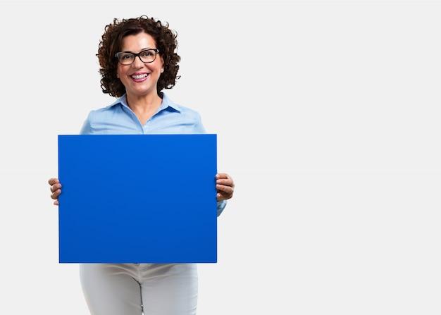 Femme d'âge moyen gaie et motivée, montrant une affiche vide où vous pouvez montrer un