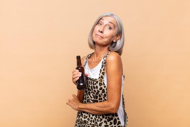 Femme d'âge moyen haussant les épaules, se sentant confus et incertain, doutant des bras croisés et regard perplexe avec une bière