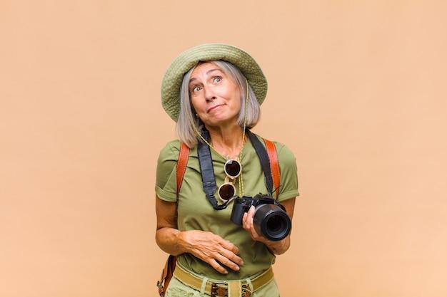 Femme d'âge moyen haussant les épaules, se sentant confus et incertain, doutant des bras croisés et regard perplexe