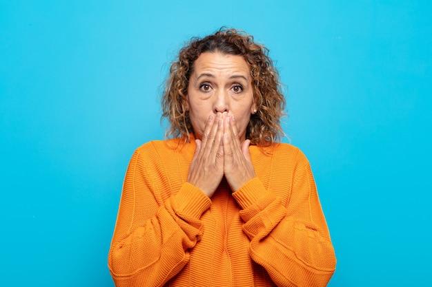 Femme d'âge moyen heureux et excité, surpris et étonné couvrant la bouche avec les mains