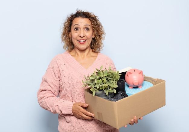 Femme d'âge moyen hispanique ayant l'air heureuse et agréablement surprise, excitée par une expression fascinée et choquée