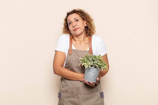 Femme d'âge moyen hispanique haussant les épaules, se sentant confus et incertain, doutant avec les bras croisés et regard perplexe