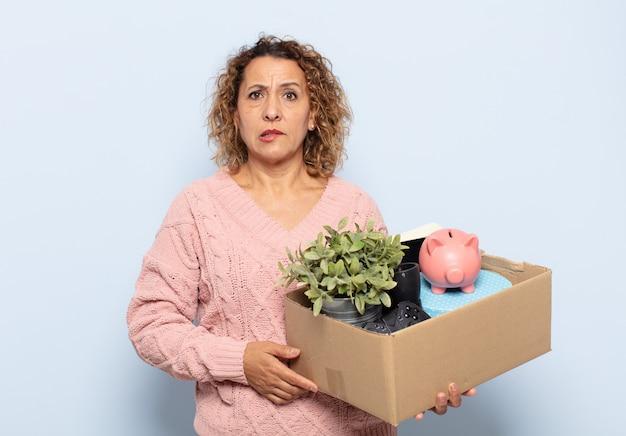 Femme d'âge moyen hispanique à la perplexité et à la confusion, mordant la lèvre avec un geste nerveux, ne sachant pas la réponse au problème