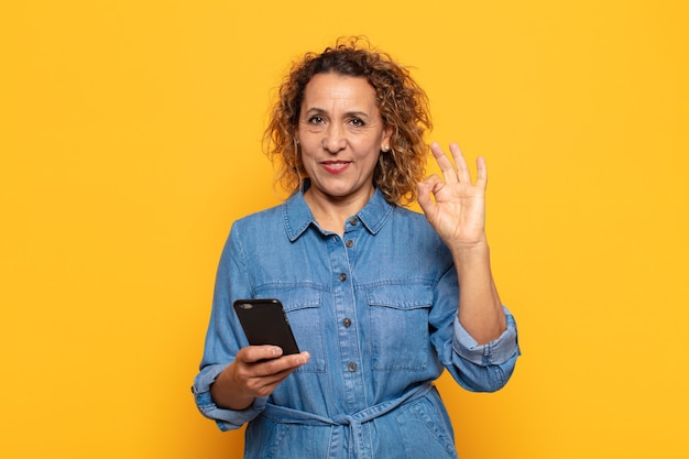 Femme d'âge moyen hispanique se sentant heureuse, détendue et satisfaite, montrant son approbation avec un geste correct, souriant
