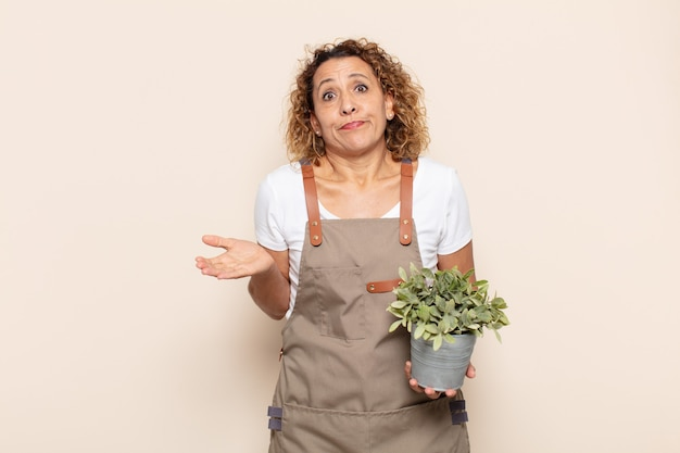 Femme d'âge moyen hispanique se sentant perplexe et confus, doutant, pondérant ou choisissant différentes options avec une expression drôle