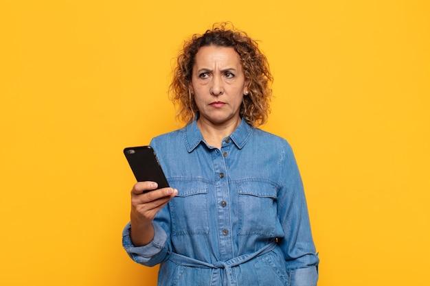 Femme d'âge moyen hispanique se sentant triste, bouleversée ou en colère et regardant sur le côté avec une attitude négative, fronçant les sourcils en désaccord