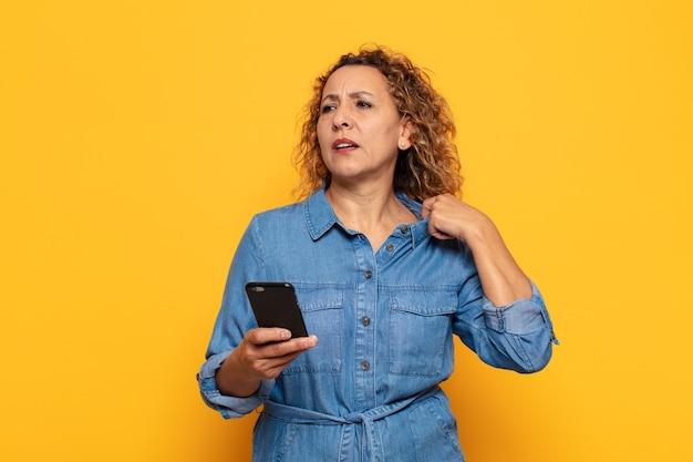 Femme d'âge moyen hispanique se sentir stressé, anxieux, fatigué et frustré, tirant le col de la chemise, à la frustration de problème