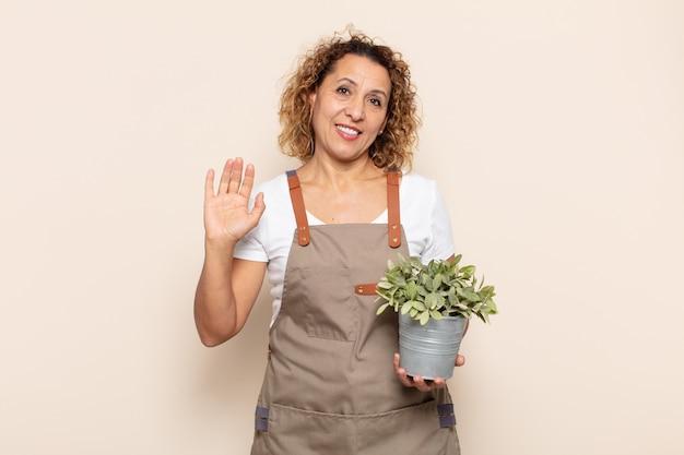 Femme d'âge moyen hispanique souriant joyeusement et gaiement, agitant la main, vous accueillant et vous saluant, ou vous disant au revoir