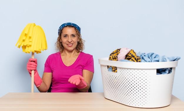 Femme d'âge moyen hispanique souriant joyeusement avec un regard amical, confiant et positif, offrant et montrant un objet ou un concept
