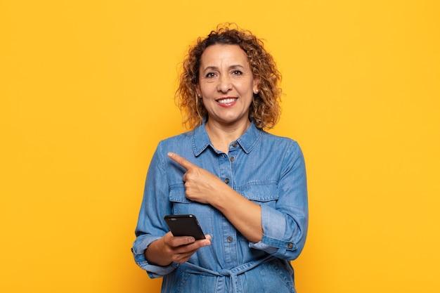 Femme d'âge moyen hispanique souriant joyeusement, se sentant heureux et pointant vers le côté et vers le haut, montrant l'objet dans l'espace de copie