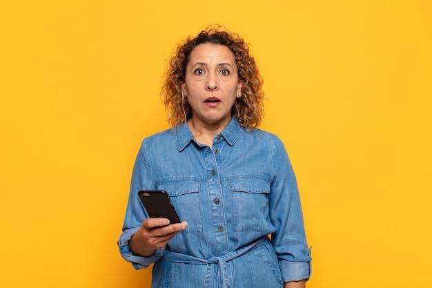 Femme d'âge moyen hispanique à très choqué ou surpris, regardant la bouche ouverte en disant wow