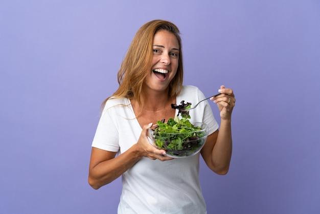 Femme d'âge moyen isolée sur mur violet tenant un bol de salade avec une expression heureuse