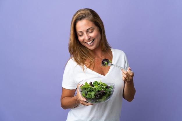 Femme d'âge moyen isolée sur mur violet tenant un bol de salade et regardant avec une expression heureuse